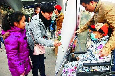 武汉:义卖鲜花筹集近万元善款铺就唐秋豪康复之路