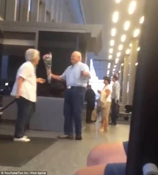 老人手持鲜花机场等老伴 感动千万网友
